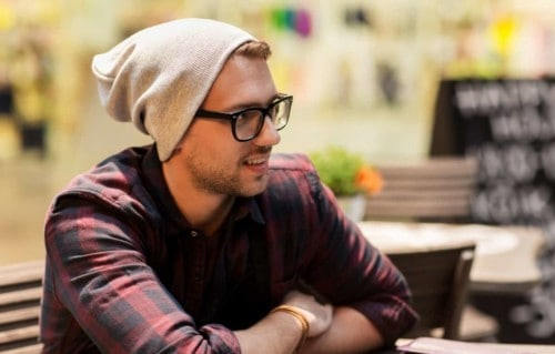 Hipster wearing a beanie and not worries about hair loss