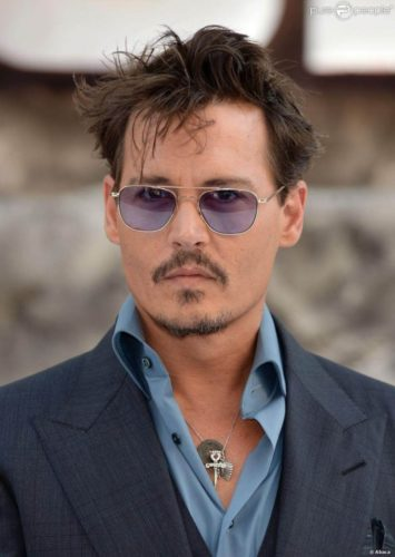 Johnny Depp with short hair and purple tinted aviator glasses.