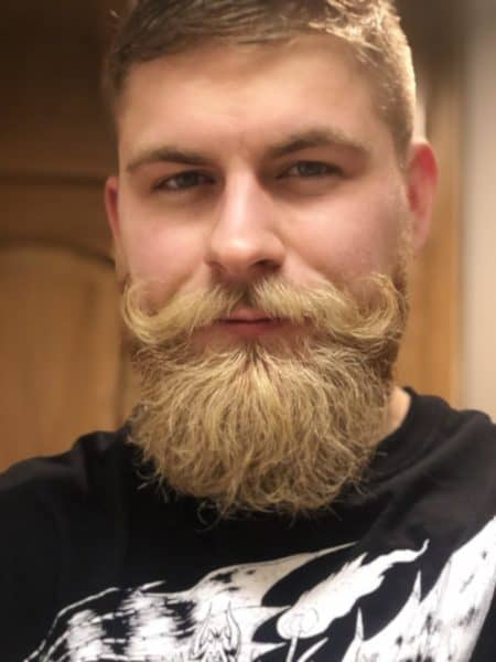 The blonde handlebar mustache creates a timeless look.