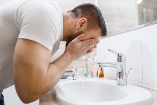 Man washes his beard in bathroom, morning hygiene