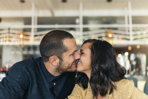 Couple kissing around beard