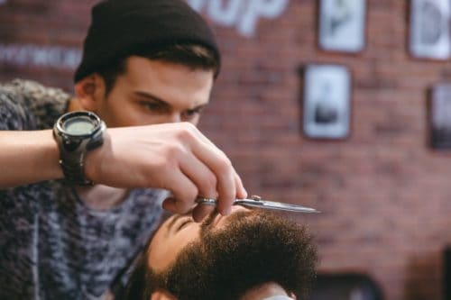 Young consentrated barber grooming beard of man with scissors